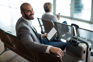 Smiling businessman with digital tablet sitting in waiting area