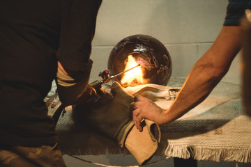 Team of glassblower blowing propane gas flame on finished piece of glass