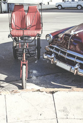 different types of transportation in a street of Cuba, a classic car and a bike with car