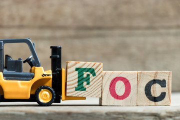 Toy yellow forklift hold letter block F to complete word FOC (Abbreviation of Free of charge) on wood background