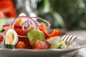 fresh vegetable salad with quail eggs in pink plate on the table