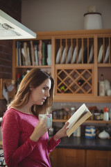 Woman reading a book while having coffee in kitchen