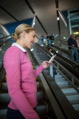 Female commuter using mobile phone on escalator