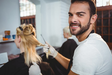 Smiling male hairdresser dyeing hair of her client at a salon