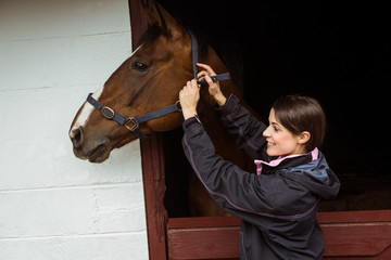 Female rider fixing saddle