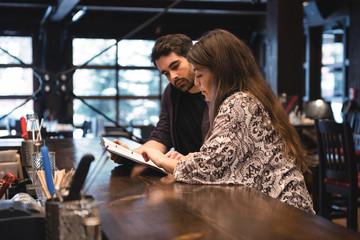 Couple looking at menu at bar counter
