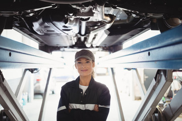 Female mechanic standing with arms crossed under a car