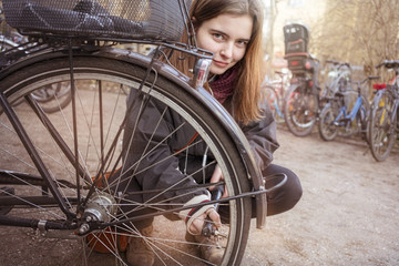 Young woman pumps up the tires of her bike