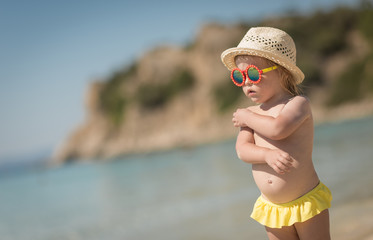 Adorable caucasian child girl with red sunglasses and hat