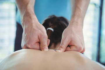 Physiotherapist giving physical therapy to the back of a female patient