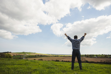 Man standing with arms raised against cloudy sky