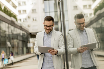 Young businessman with digital tablet by the office building