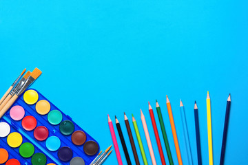 Palette with Rows of Multicolored Watercolor Paints Brushes Pencils on Blue Background. Arts School Class Creativity Painting Hobbies Kids Education Concept. Poster Banner Streamer Template