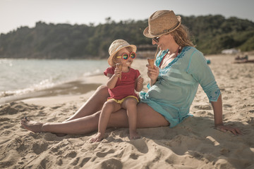 Mother with child on tropical beach ieating icecream