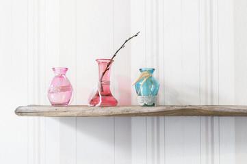 Drei pastellfarbige Glasvasen mit Weidenkätzchen Ast stehen auf altem Holz