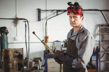 Portrait of welder standing in workshop