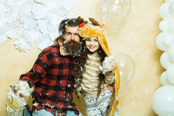 Happy christmas cute small girl or pretty child in winter hat and bearded man in checkered shirt with feathers on face, near silver and white balloons and decorative new year snowflakes
