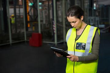 Female worker using digital tablet in warehouse