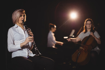 Three female students playing double bass, clarinet and piano