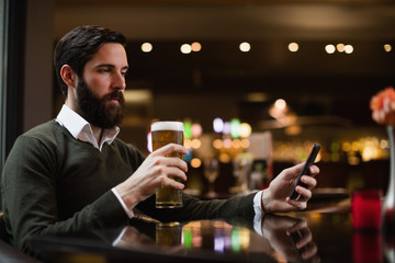Man looking at mobile phone while having glass of beer