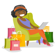 Young african-american woman sitting on the armchair among shopping bags with a laptop computer. Woman doing online shopping. Vector cartoon illustration isolated on white background. Square layout.