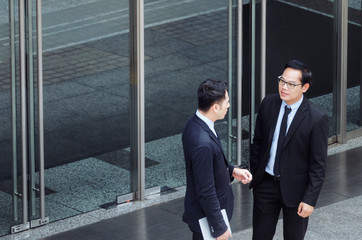two business young asian smart man talking information about finance news together standing in front of Bank in city, congratulation, success, meeting, partner, teamwork, community, connection concept