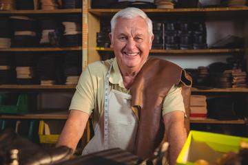 Portrait of shoemaker sitting in workshop