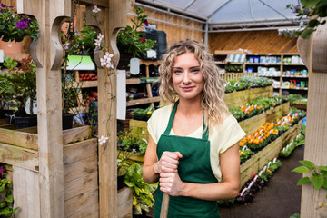 Smiling female florist standing in garden center