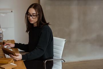 Female executive examining a wooden slab at desk
