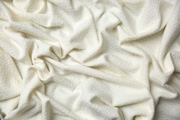 Cotton blanket with an interesting texture and crumpled irregularly in a rather artistic way.