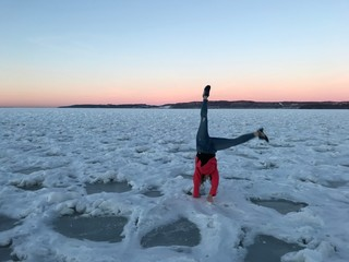 Woman is doing a handstand on frozen lake at sunset