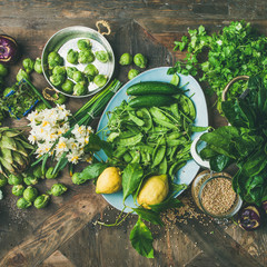 Wall Mural - Spring healthy vegan food cooking ingredients. Flat-lay of vegetables, fruit, seeds, sprouts, flowers, greens over wooden background, top view, square crop. Diet, clean eating food concept