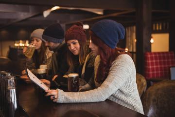 Friends holding menu at bar counter