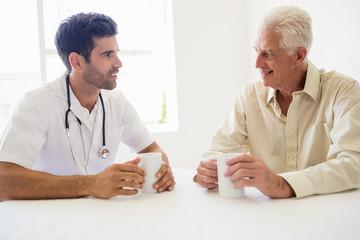 Nurse and senior man drinking coffee