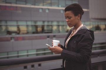 Businesswoman using mobile phone while standing by railing