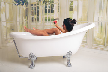 Girl having fun in the tub. She is in a spacious and elegant bathroom