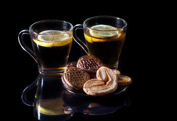 Black tea with a lemon, with cookies in a glass cup, with reflection on a black background.