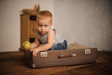 Little boy sitting in the suitcase and holding an apple