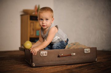 Cute little boy sitting in the suitcase and holding an apple