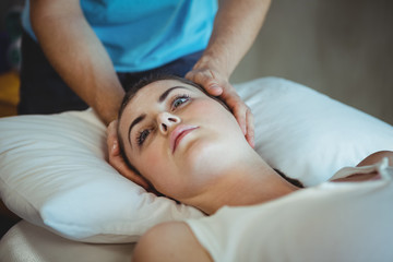 Male physiotherapist giving head massage to female patient