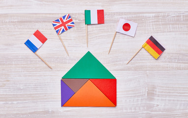 A colored house, assembled from geometric figures, with flags of different countries. Concept for language courses, translators, etc.