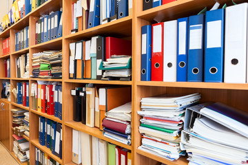 A lot of files folder store in the office shelf: papers, documents and catalogs