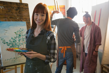 Portrait of woman holding color palette while friends painting in background