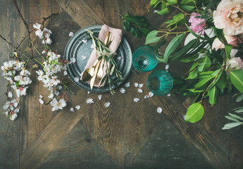 Flat-lay of Spring Easter holiday Table setting. Tender almond blossom flowers on branches and peonies, plates, glasses and cutlery over vintage wooden table background, top view, copy space