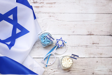 Israeli flag and items with national colors on a wooden background
