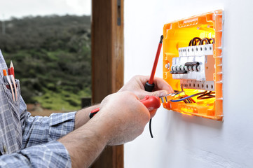 Electrician technician repairs the electrical panel of a residential system