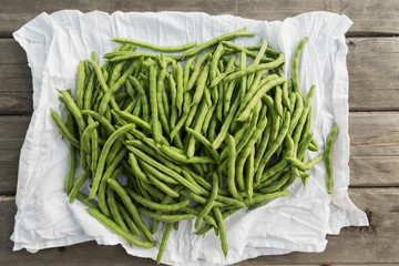Close-up of green beans on white cloth against wooden background