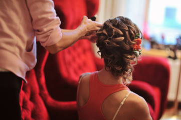 Close up of a beautiful wedding hairstyle with fresh flowers. Orange color