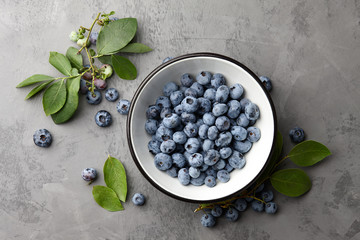 Fresh ripe blueberries with leaves in bowl on gray stone background, top view
