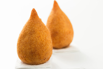 Coxinha is a deep fried food, traditional in Brazil. Two snacks on white background. Selective focus, minimalism.